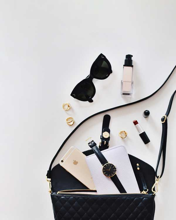 sac a main avec des lunettes de soleil une montre un smartphone un rouge a levres des bagues et du fond de teint