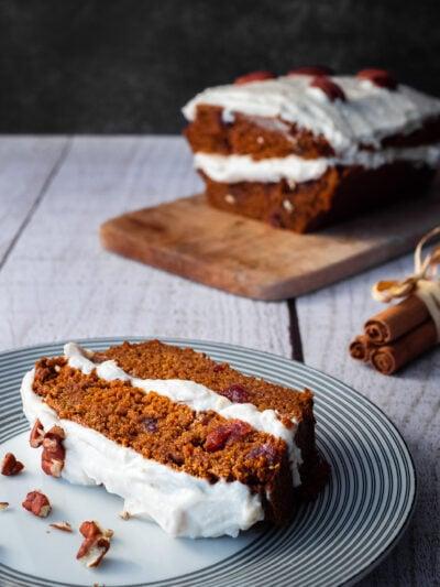 une part de carrot cake dans une assiette à dessert sur une table en bois avec des bâtons de cannelle et le carrot cake sur une planche a découper en arrière plan