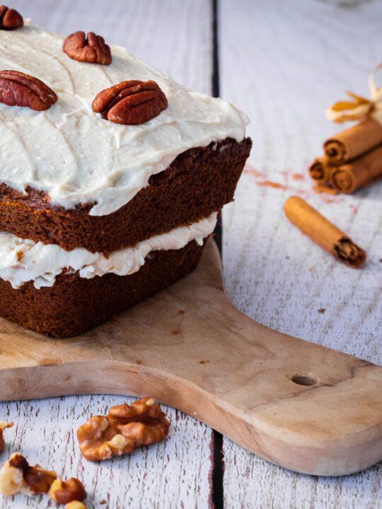un carrot cake vegan avec son glaçage ses noix de pécan sur une planche a decouper sur une table en bois avec des bâtons de cannelle et des cerneaux de noix