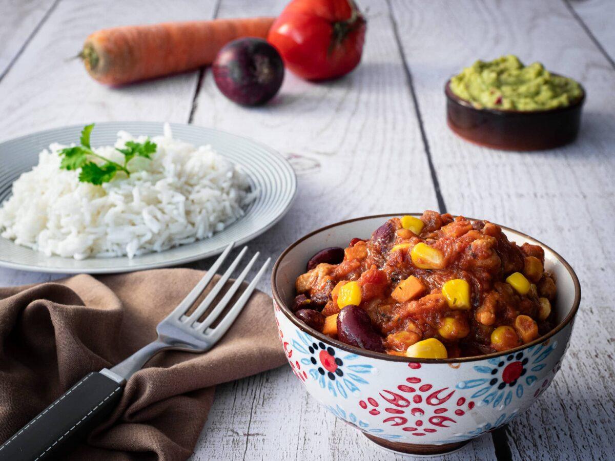 une part de chili sin carne dans un bol servi avec une assiette de riz et un guacamole