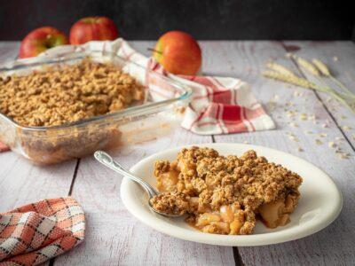 une grosse part de crumble dans une assiette blanche avec une cuillere et une serviette avec le plat de crumble des pommes et des épis de blés en arrière plan
