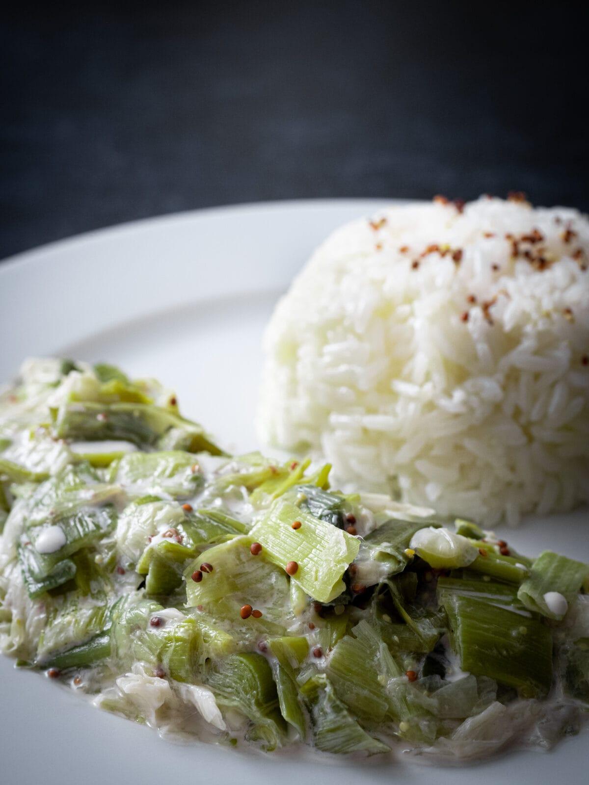 gros plan sur la fondue de poireaux a la creme vegan avec du riz dans une assiette blanche sur un fond noir