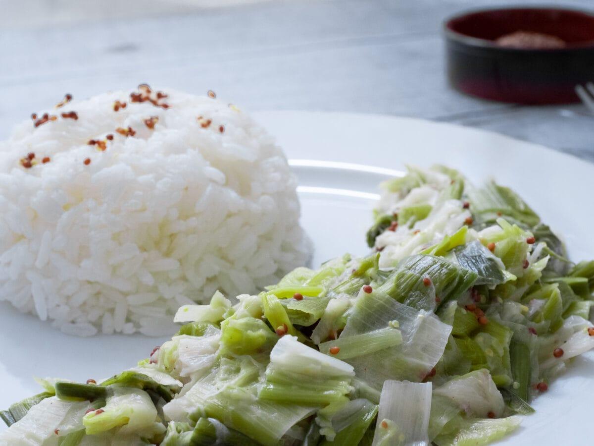gros plan sur une assiette de fondue de poireaux avec un dome de riz et un ramequin de moutarde en arriere plan
