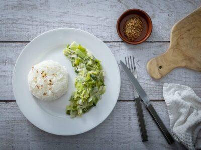 assiette de fondue de poireaux avec du riz un ramequin de moutarde à l'ancienne des couverts une planche a découper et une serviette sur une table en bois
