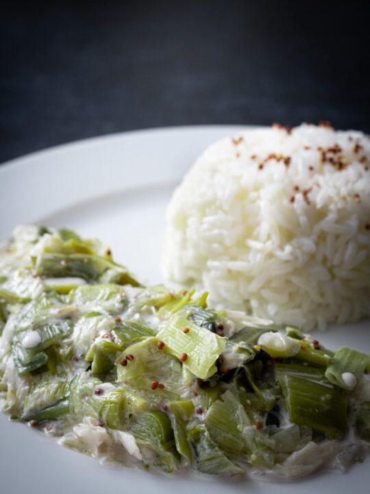 gros plan sur la fondue de poireaux a la crème vegan avec du riz dans une assiette blanche sur un fond noir
