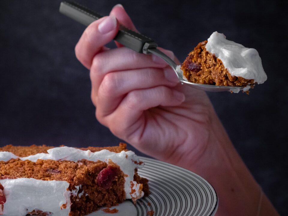une cuillère d'une part de carrot cake vegan avec ses cranberries et noix et recouvert d'un glaçage cream cheese vegan à base de yaourt au soja