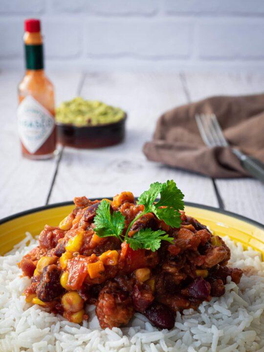 assiette de chili sin carne servie sur du riz avec de la coriandre avec du tabasco et du guacamole en arrière plan