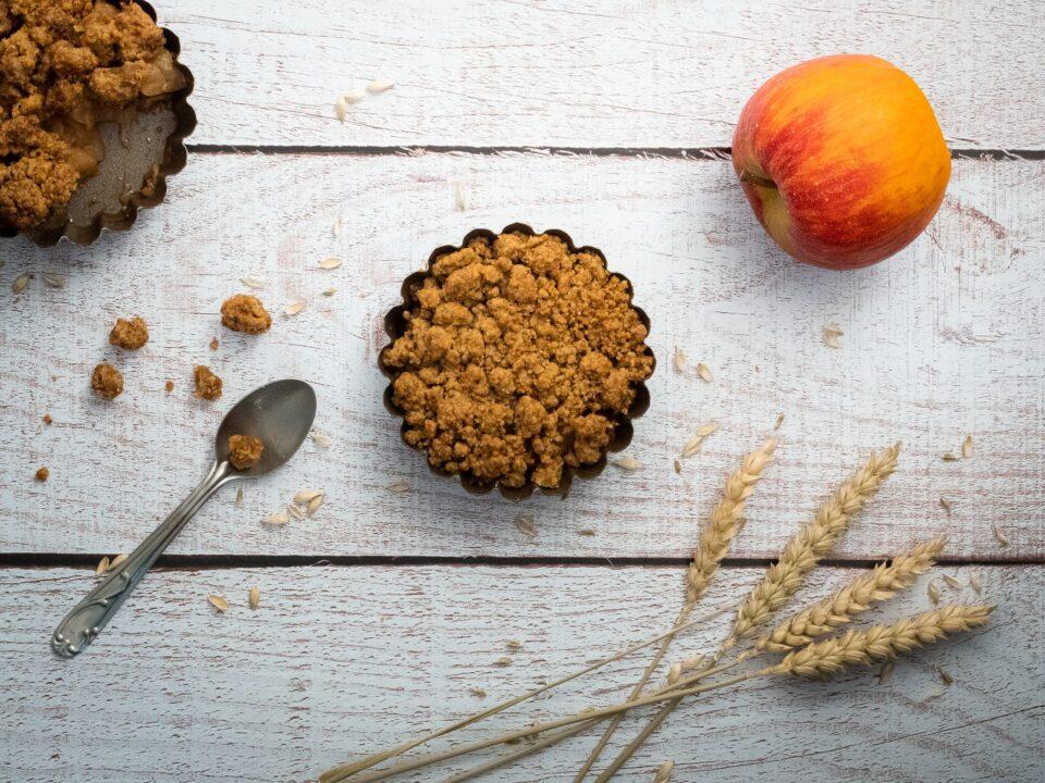 une part individuelle de crumble entourée d'une part entamée d'une pomme d'épis de blés et d'une cuillère