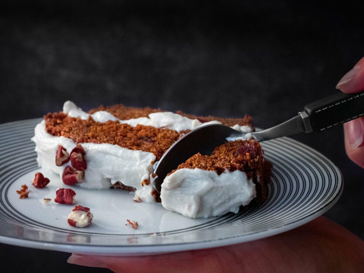 une cuillere decoupe un morceau du delicieux carrot cake vegan avec des noix de pecan des cranberries et un genereux glacage vegan
