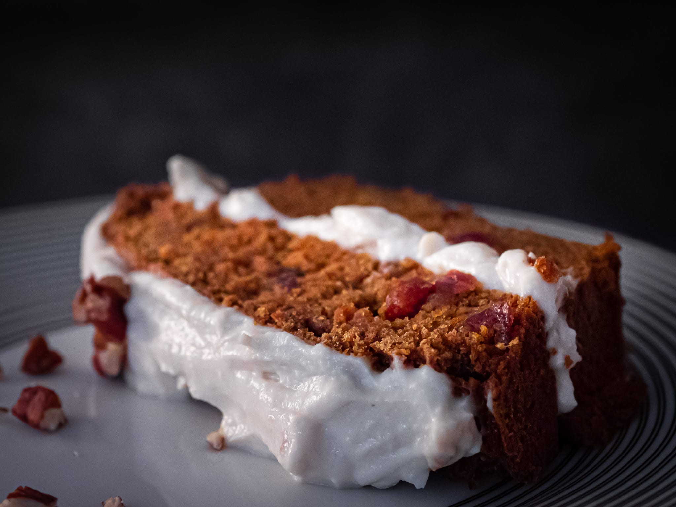 une part de carrot cake vegan avec des noix de pécan des cranberries et un glaçage vegan