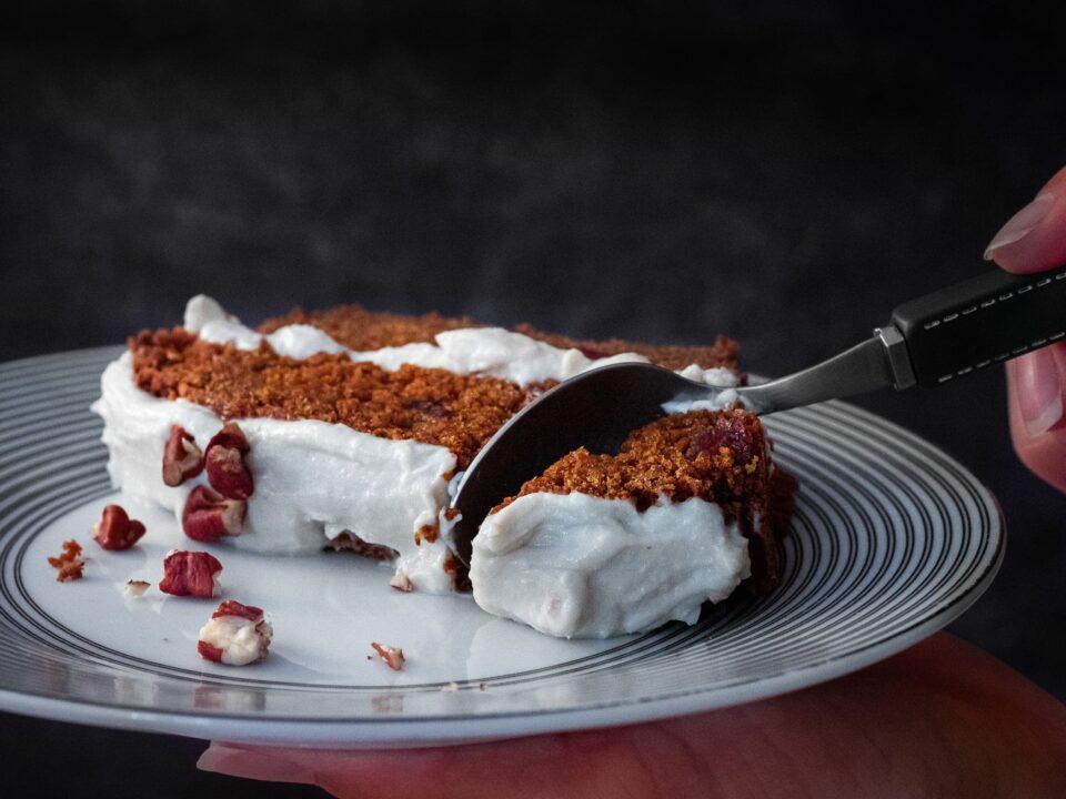 une cuillère découpe un morceau de carrot cake vegan avec des noix de pécan des cranberries et un glaçage vegan