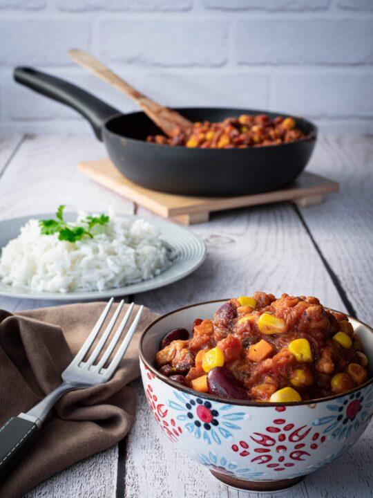 une part de chili sin carne dans un bol avec une assiette de riz et la poêle remplie de chili sin carne en arrière plan