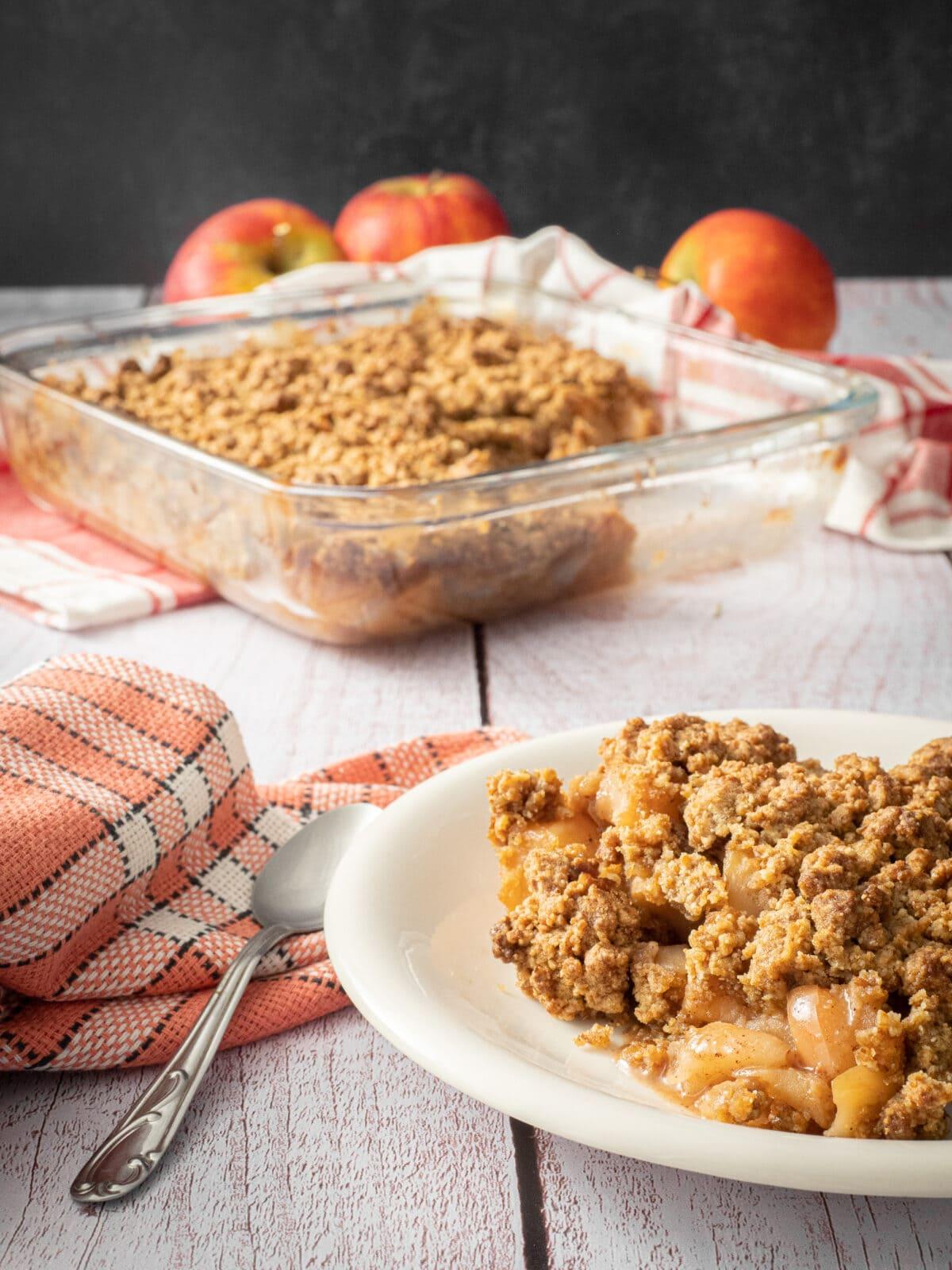 une grosse part de crumble dans une assiette blanche avec une cuillère et une serviette avec le plat de crumble et des pommes en arrière plan