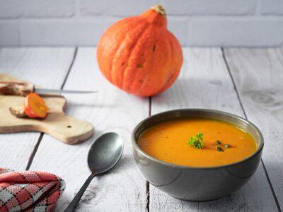 soupe de potimarron avec une feuille de persil et des graines de courge sur une table en bois avec une serviette et un potimarron en arrière plan